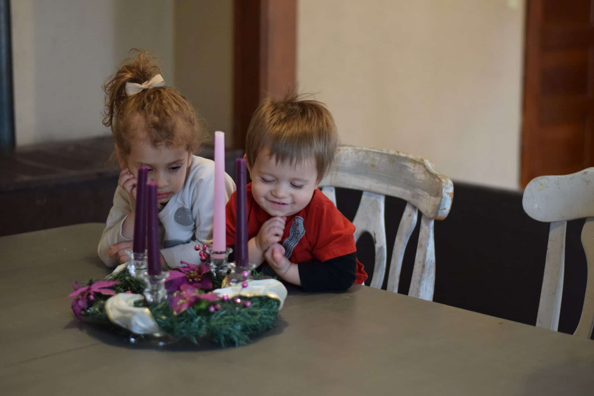 little girl and boy admiring the advent wreath at the dining room table
