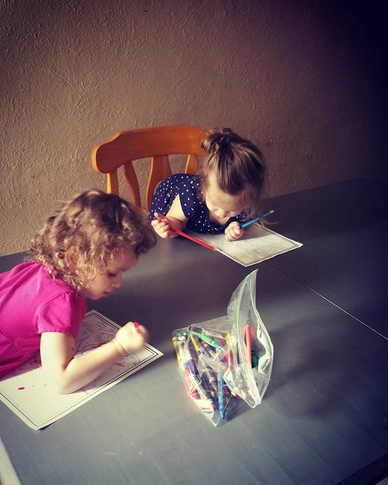 two little girls coloring at dining room table