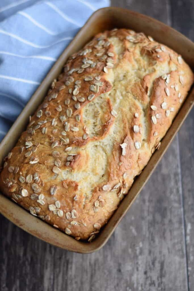 close up image of fresh baked honey oat bread in a stoneware bread pan