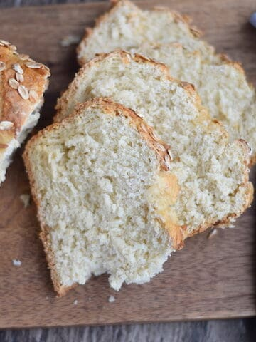 sliced up honey oat bread on a wooden board