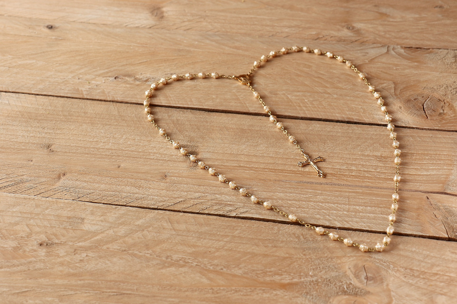 rosary in shape of a heart displayed on wooden table
