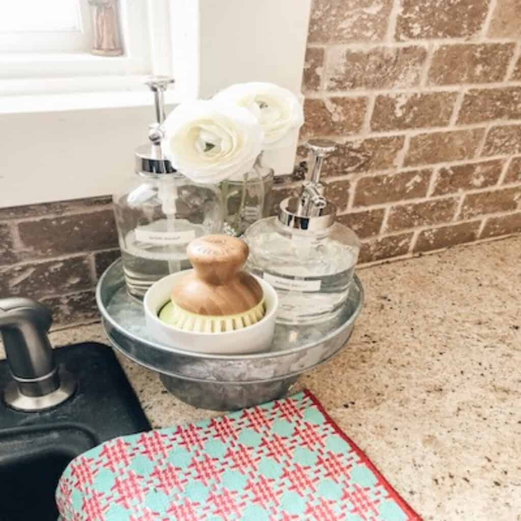 cake stand with natural soap brush and dish soap in clear jars
