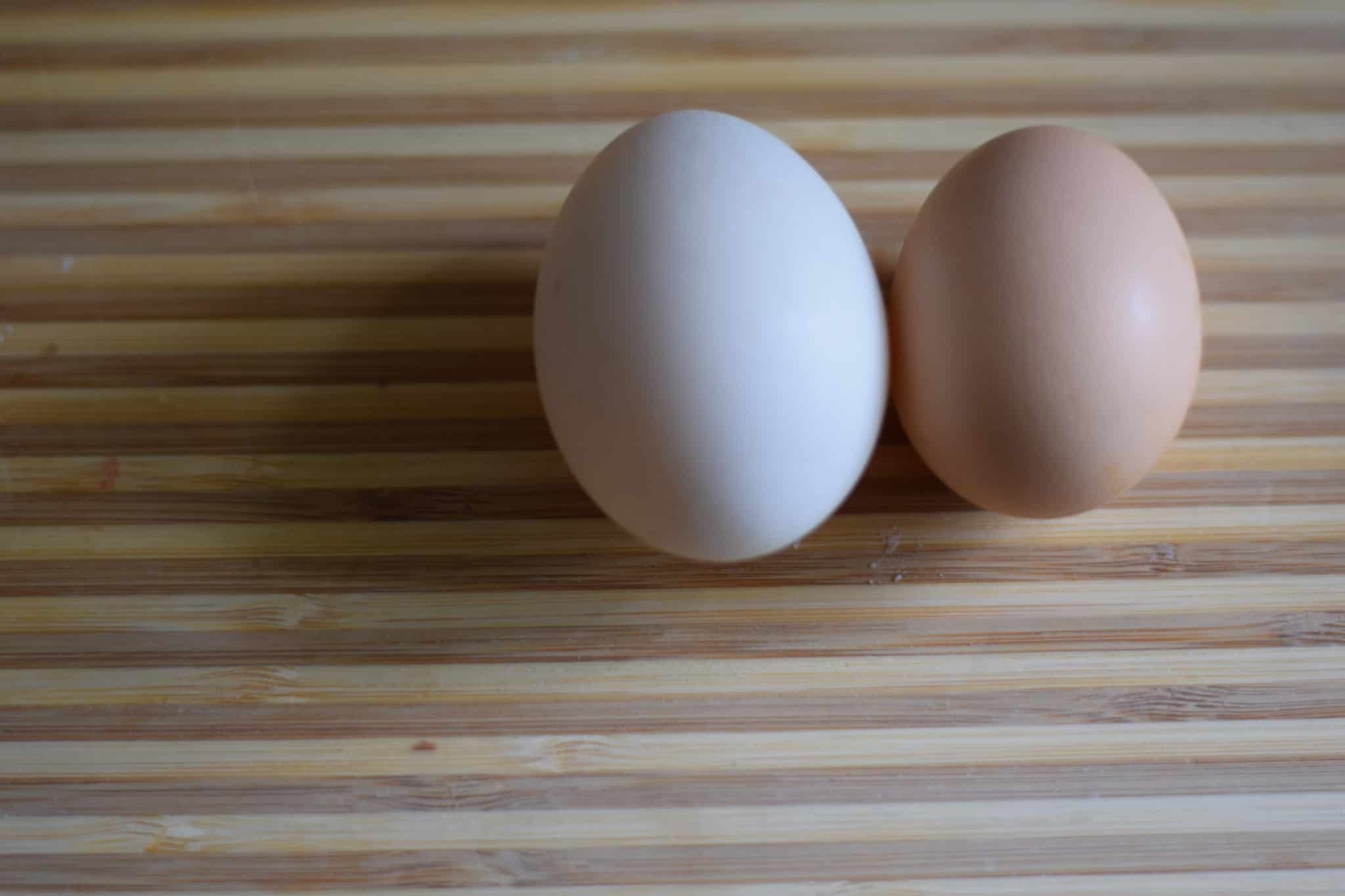 duck egg next to a chicken egg on a wooden cutting board
