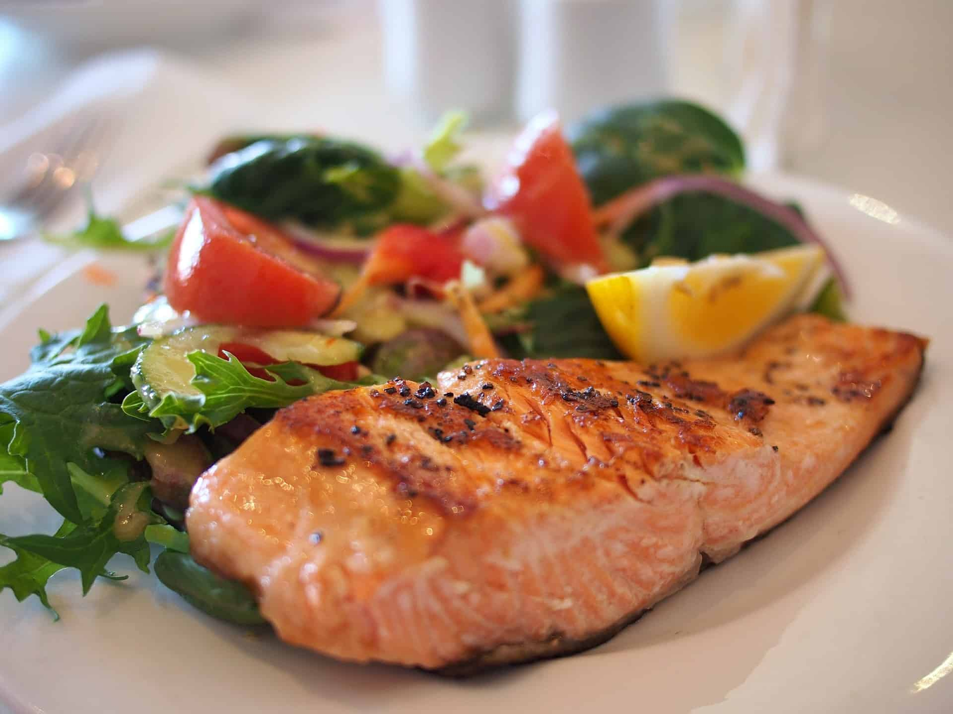 baked salmon and green leafy salad with tomatoes