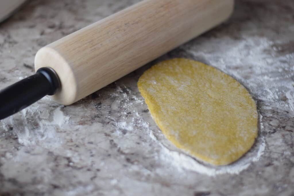 pasta dough rolling out on countertop with a wooden rolling pin