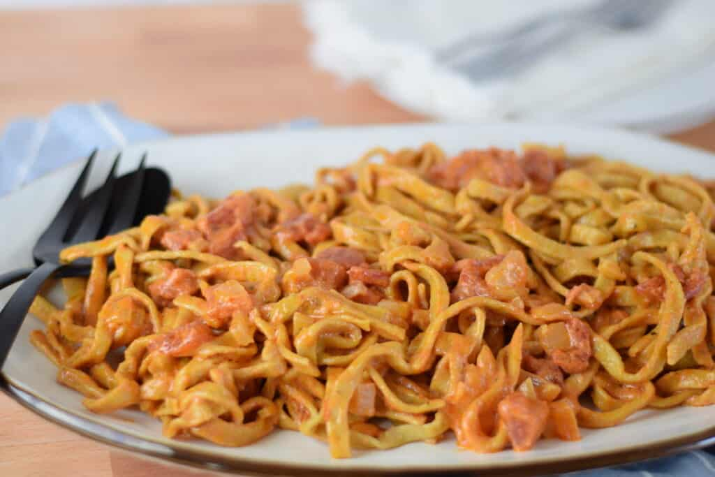 cooked homemade pasta noodles with a creamy pomodoro sauce on a white platter with black utensils