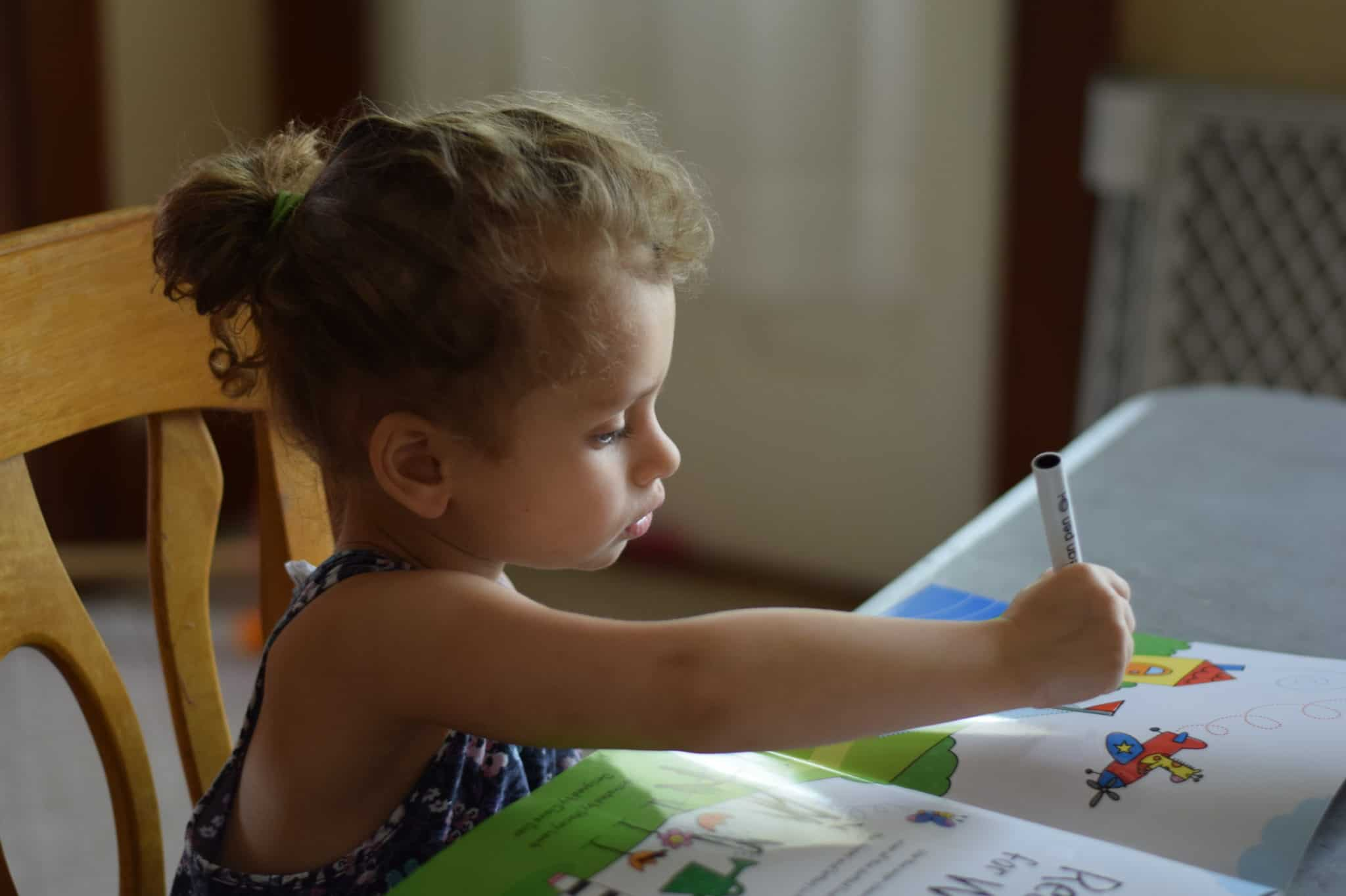 little girl sitting at a table doing school work