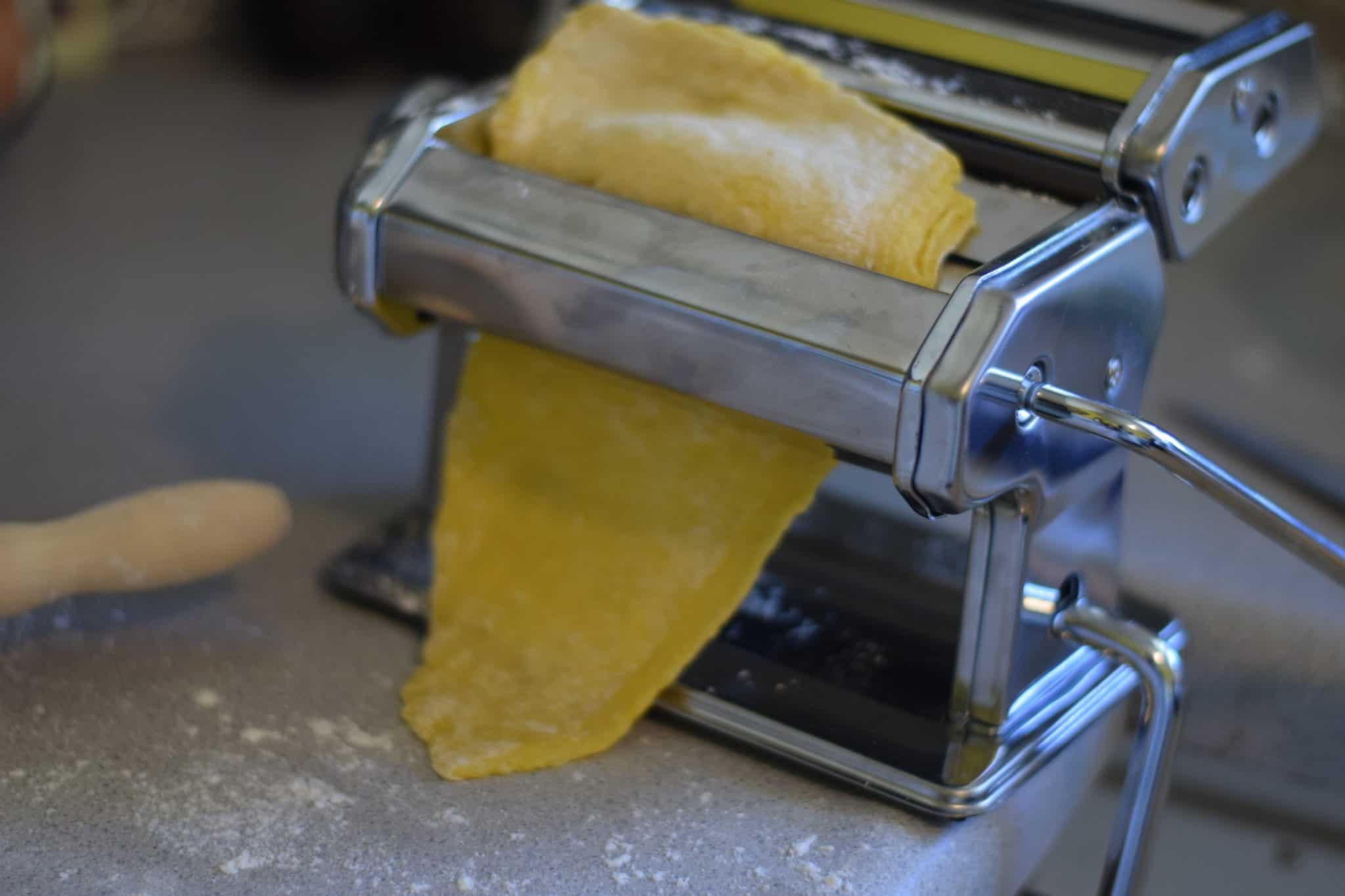 rolling pasta dough through pasta machine