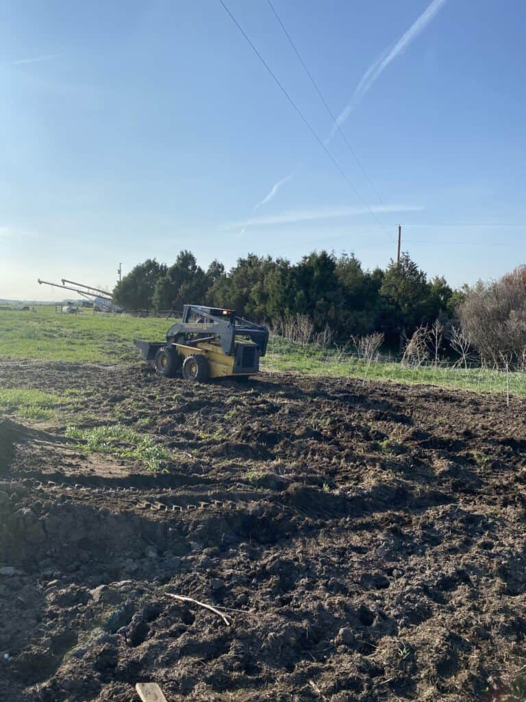 using a skid steer to prepare the ground for the garden