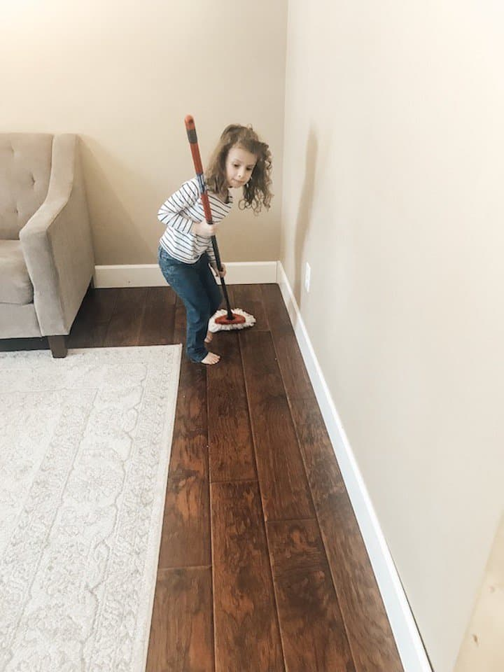 little girl helping to mop the wood floor