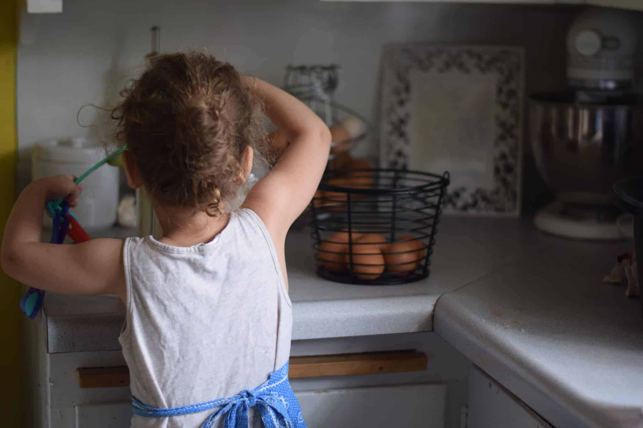 little girl measuring flour in a kitchen