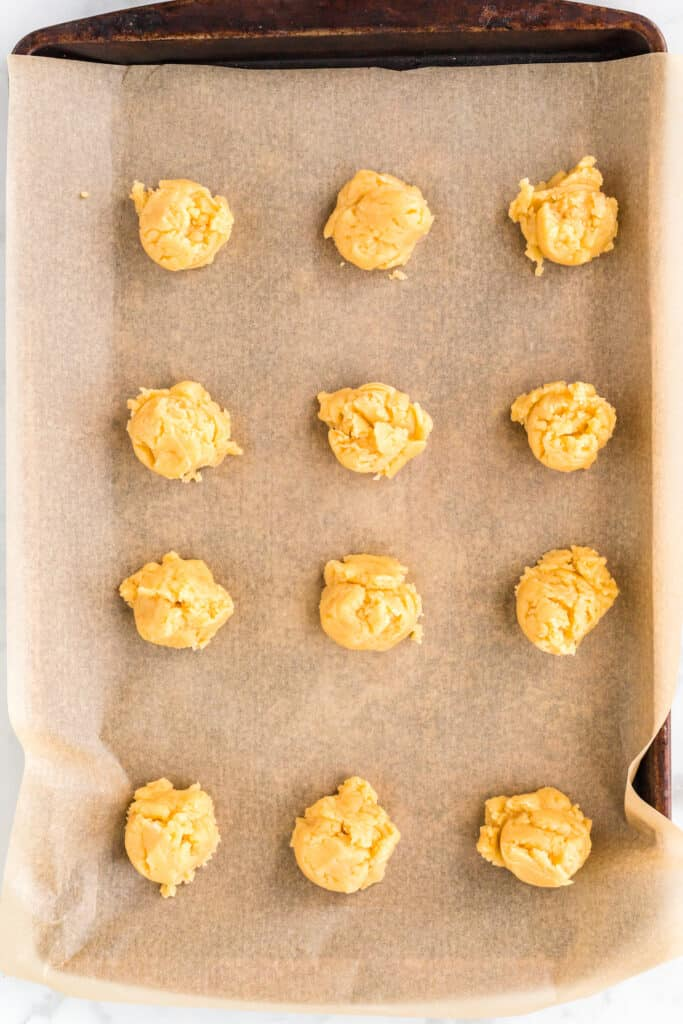 honey butter cookies scooped out and on a baking sheet with parchment paper