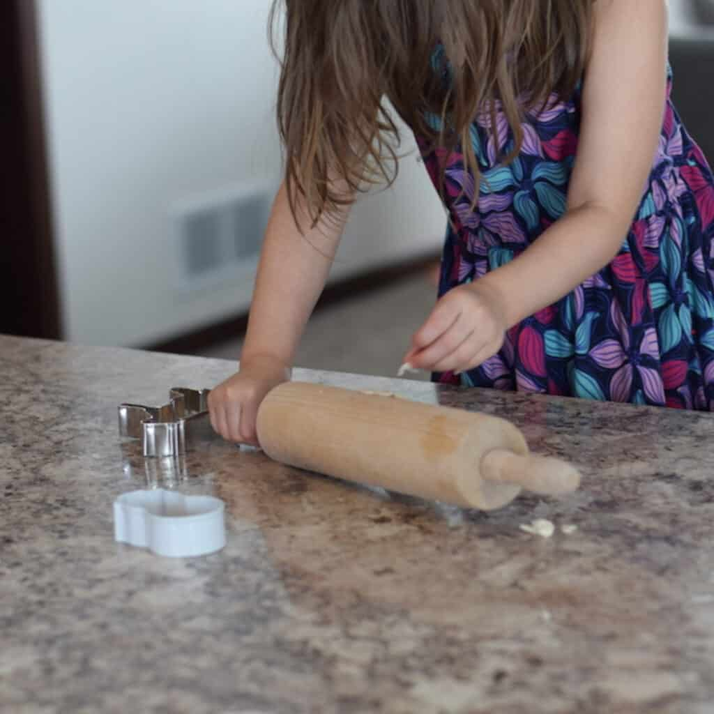 little girl rolling out dough on counter top