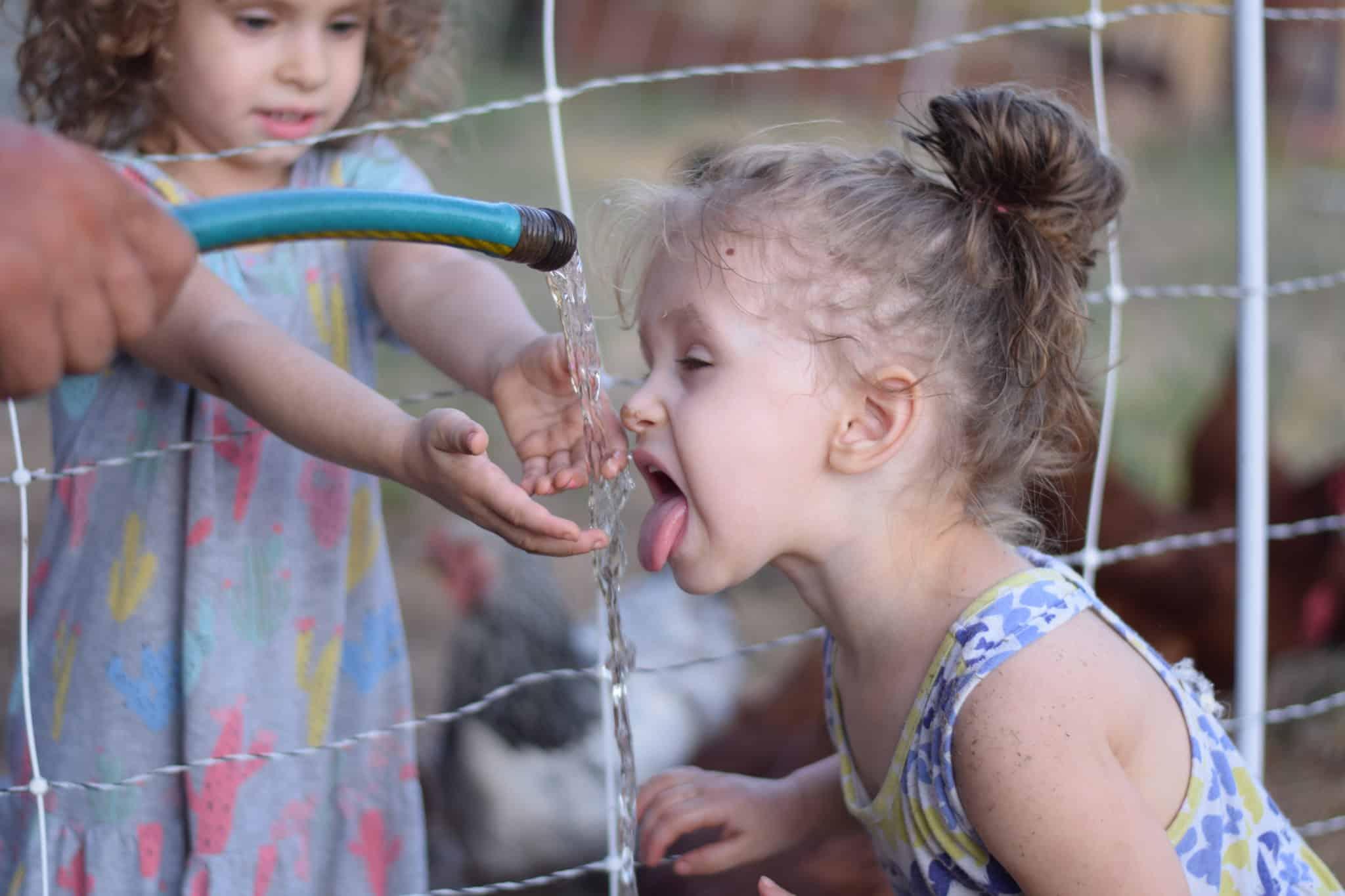 little girl drinking from a garden hose