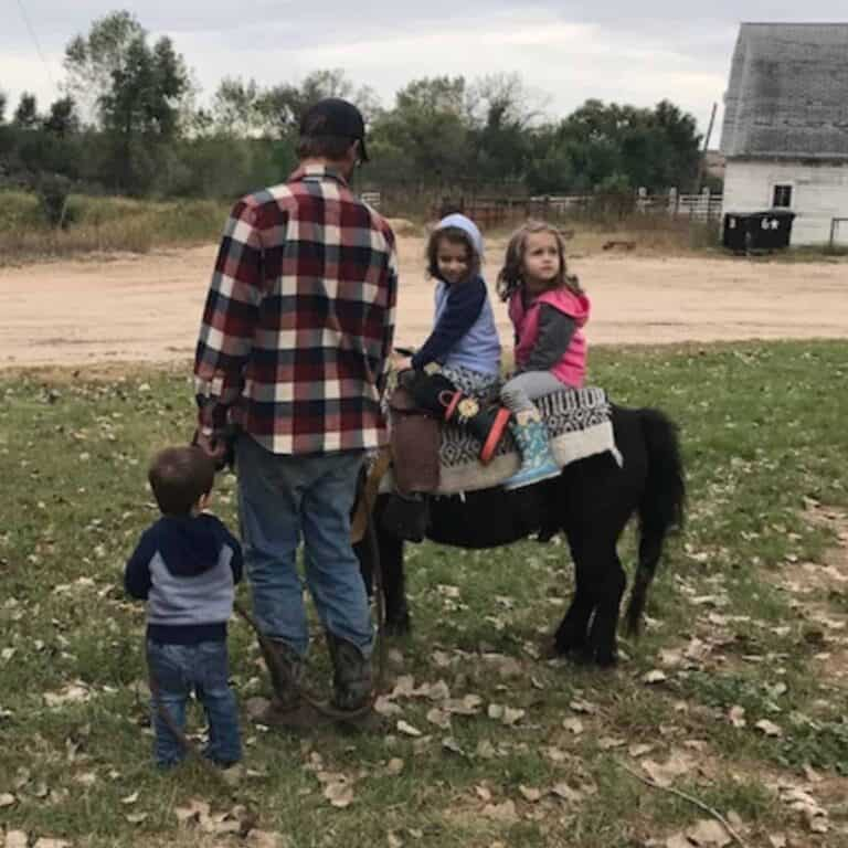 children in country with a mini horse