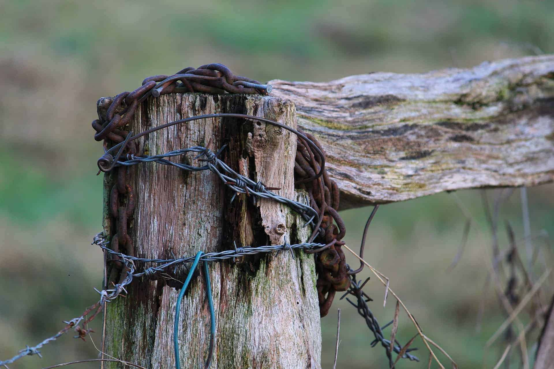 wooden fence post with barbed wire wrapped around it