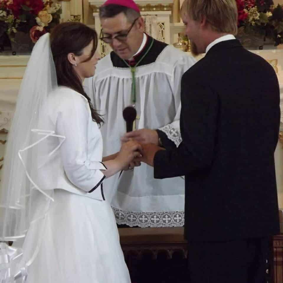 husband and wife at the altar with priest saying wedding vows