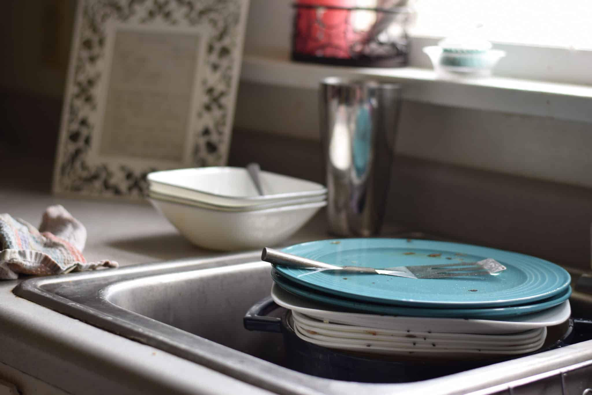 pile of dirty dishes in sink