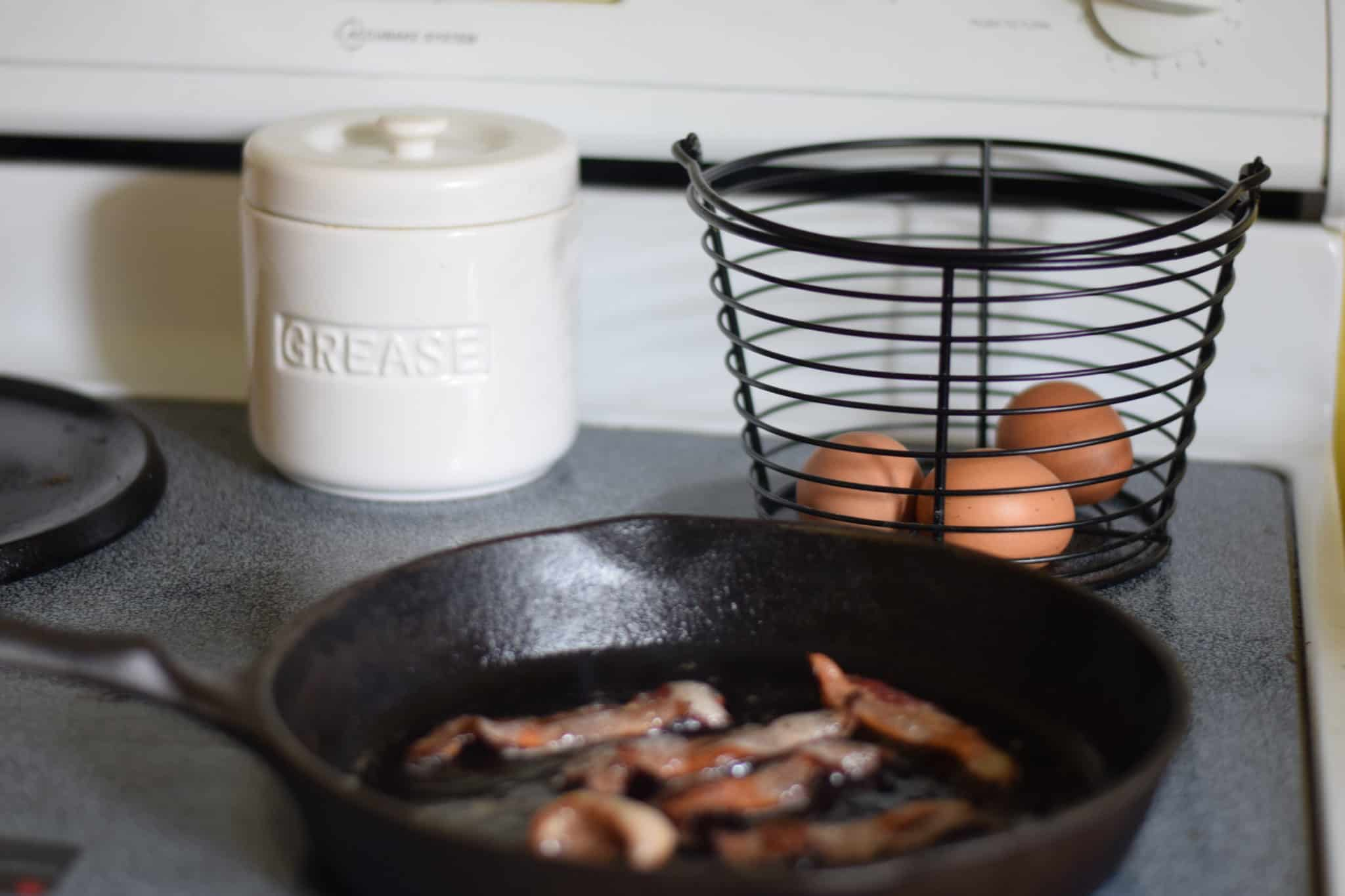 bacon cooking in a cast iron skillet
