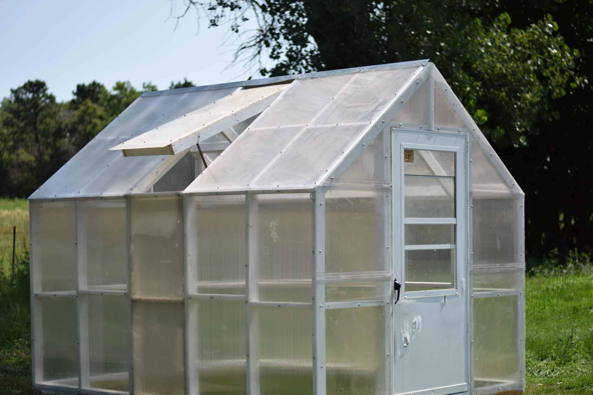 Completed greenhouse in outdoor garden with trees in background.