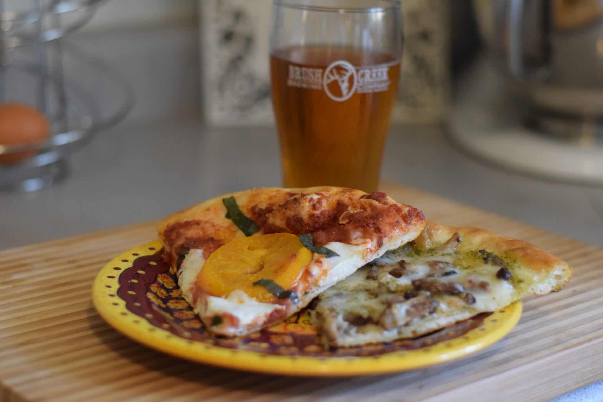 pizza on a plate and beer in cup in background