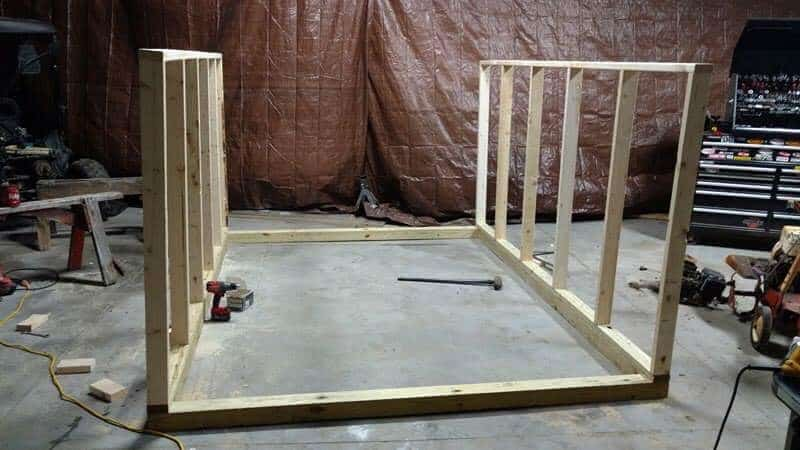 The wall frames of the greenhouse being constructed inside of the shop.