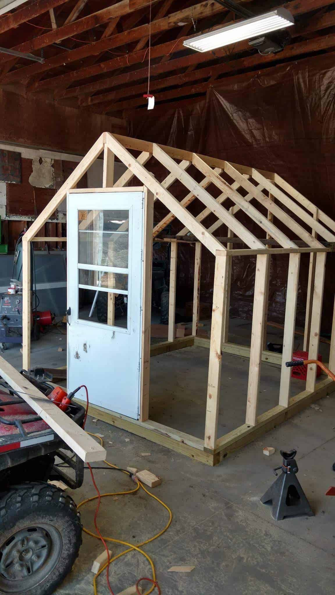 The greenhouse wall frames and roof frame are constructed and the white screen door has been added to the door frame.