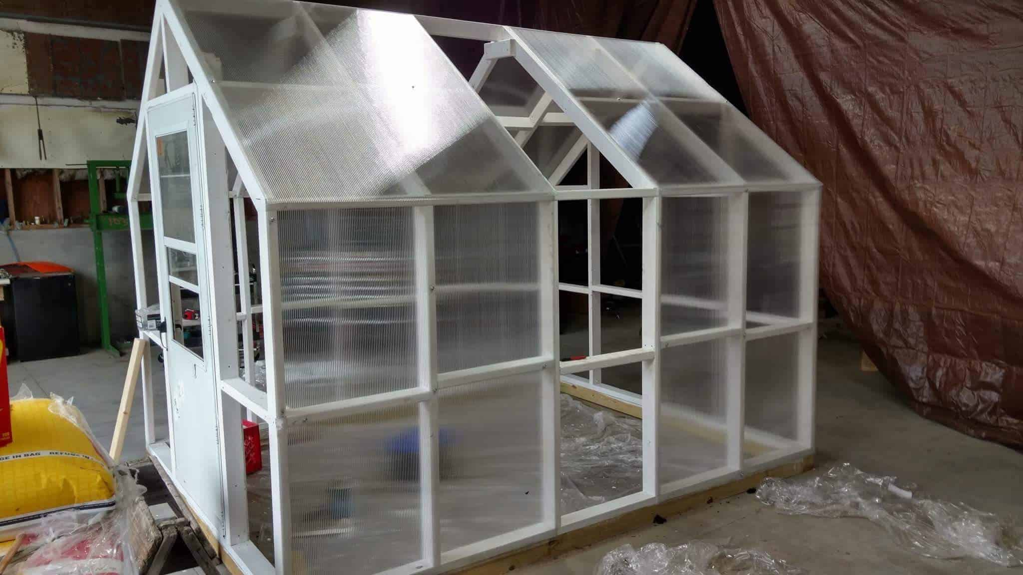 Polycarbonate plastic sheeting is being installed on the greenhouse and the frame has been painted white.