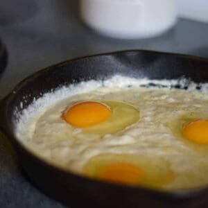 poaching eggs in cream sauce with a cast iron skillet