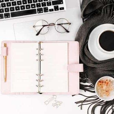 planner with a laptop, cup of coffee, and reading glasses