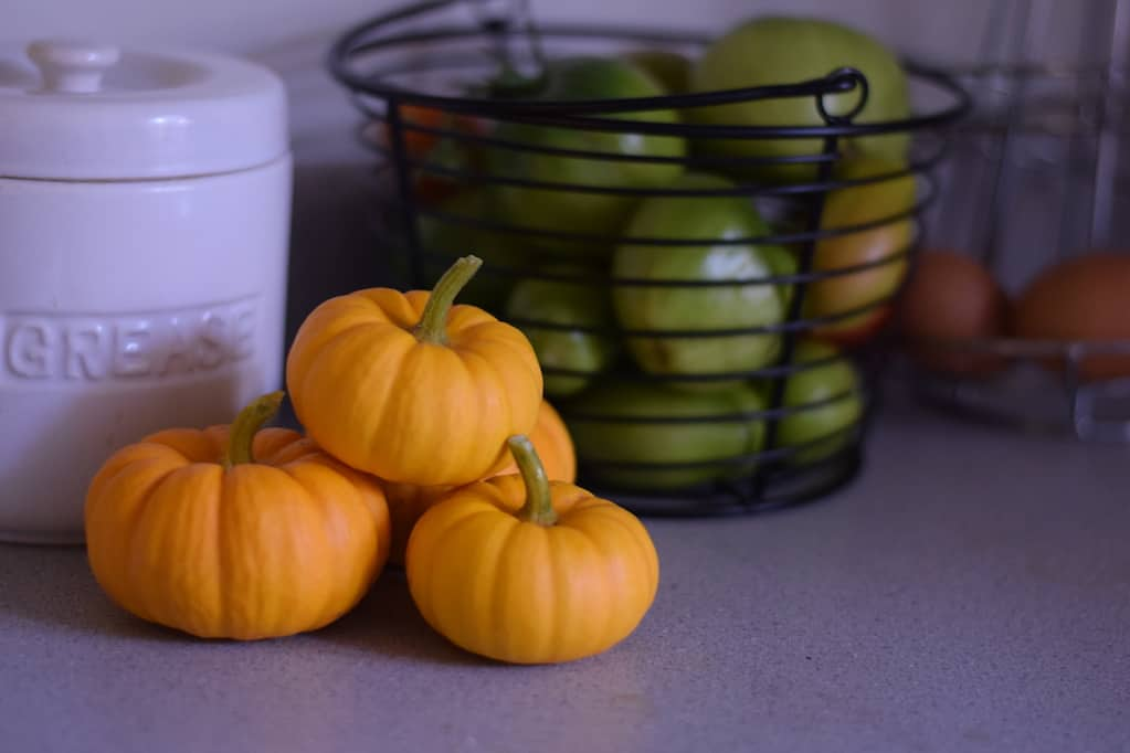 mini pumpkins and green tomatoes in a basket
