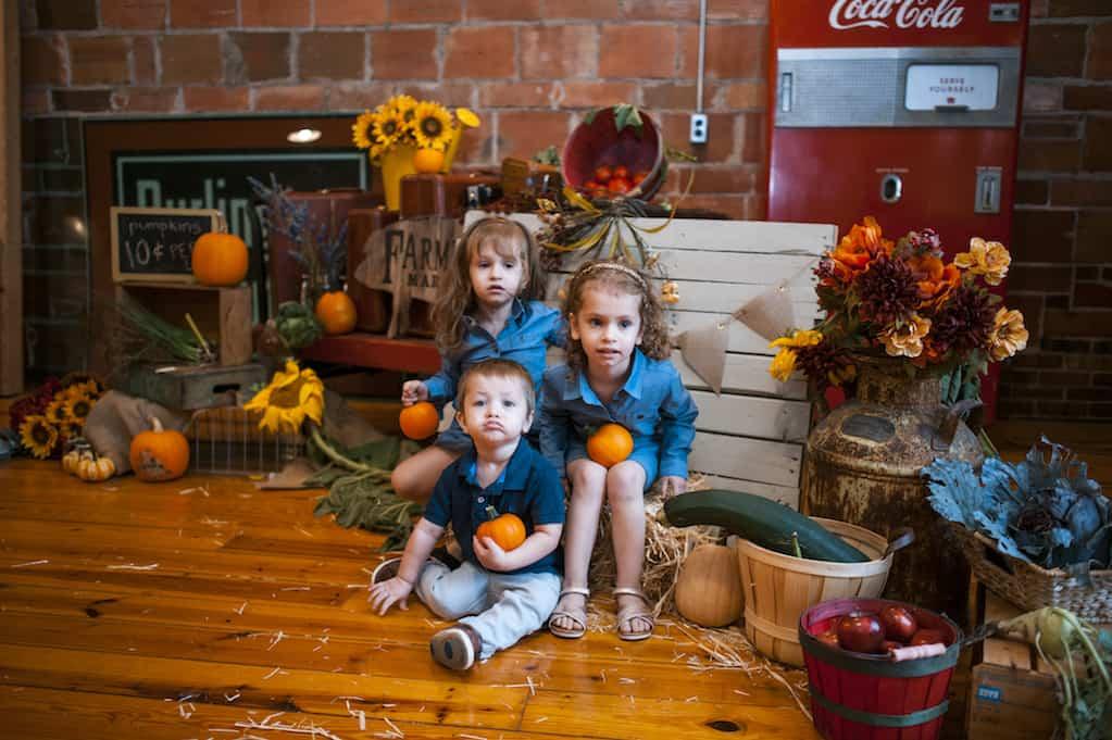 little children holding small pumpkins