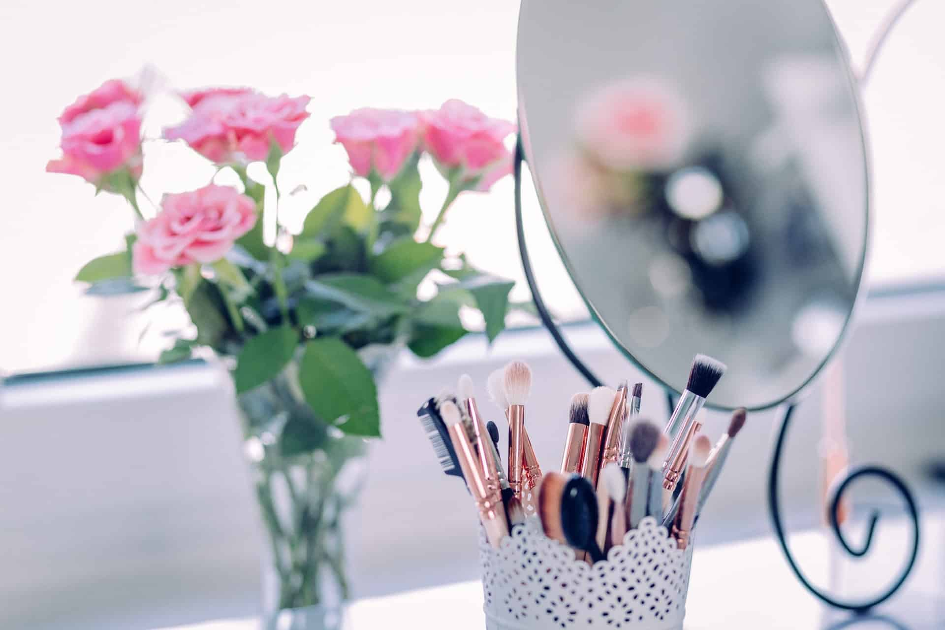 vanity with makeup brushes, mirror, and pink roses in a vase