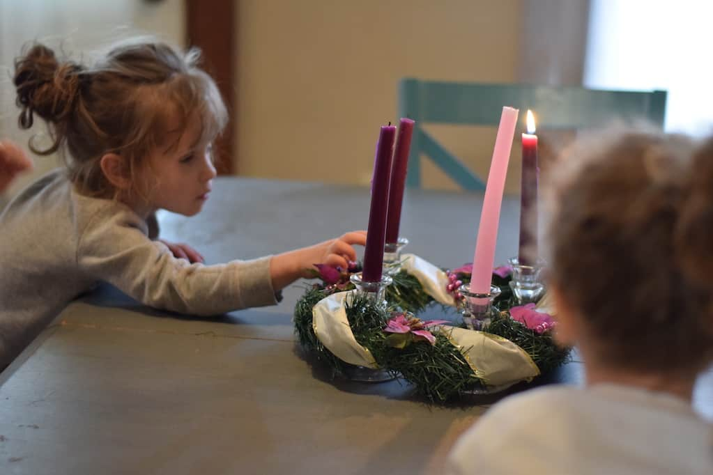 two little girls admiring the advent wreath at the dining room table