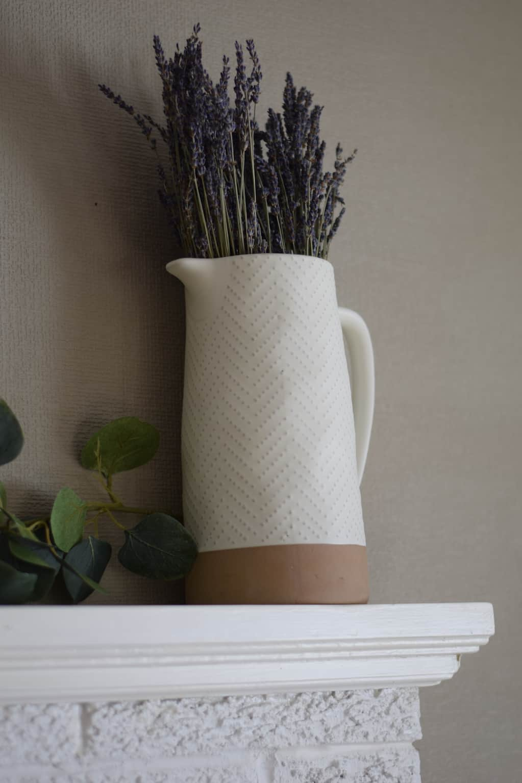 white vase filled with dried lavender on top of the mantel