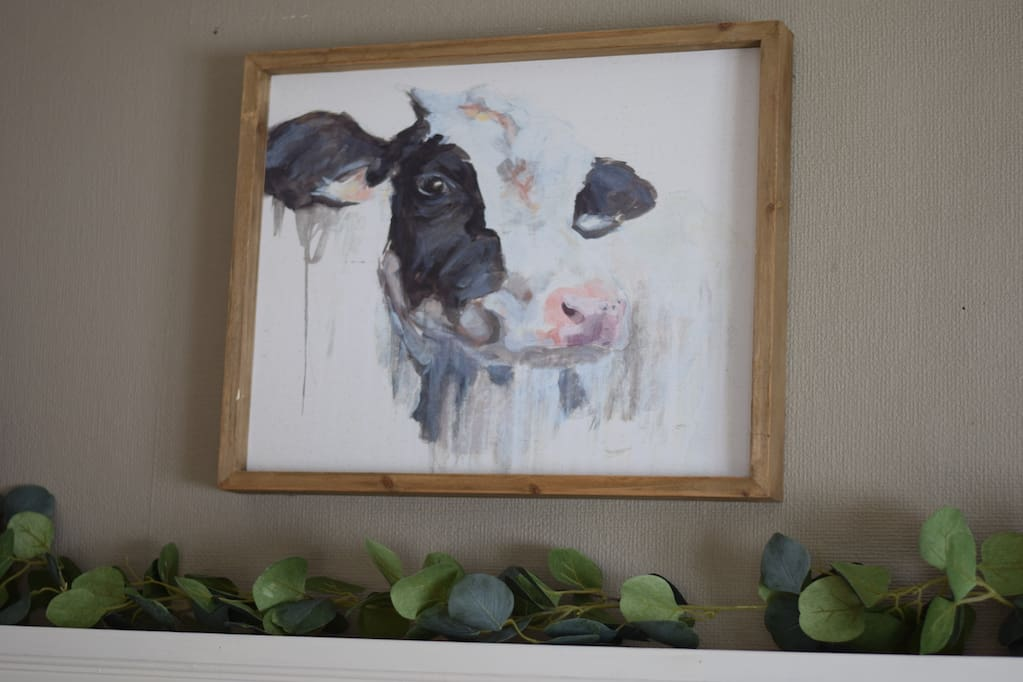 Cow picture and eucalyptus garland above mantel