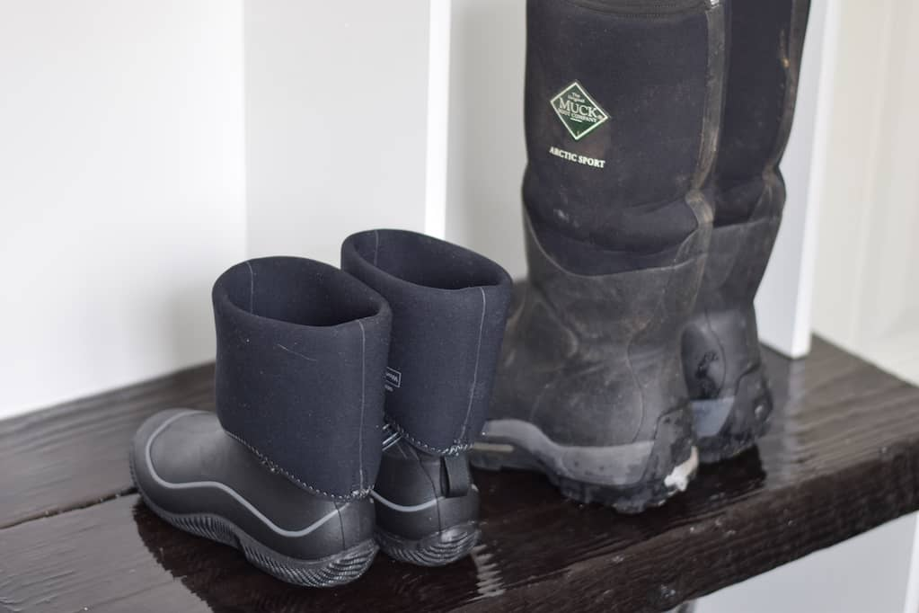 his and her muck boots on a bench in the mudroom