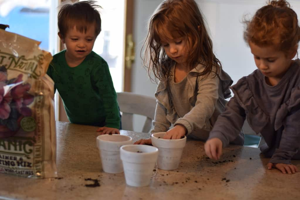 children help plant seeds in easy diy rustic herb planters