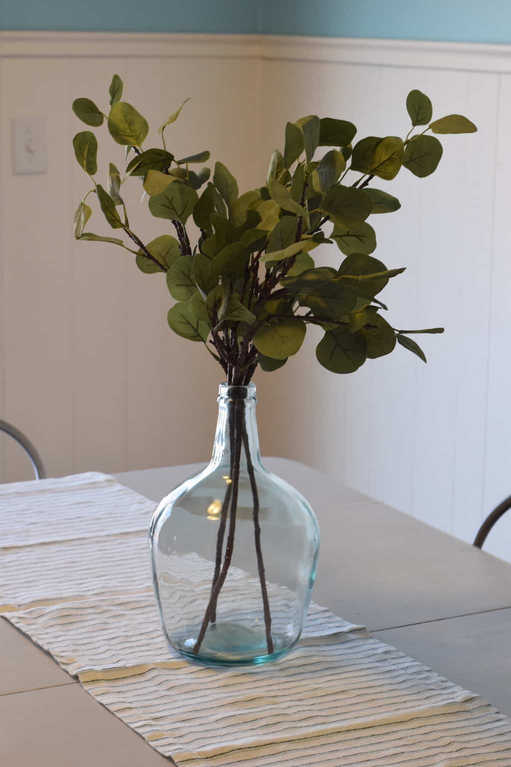 eucalyptus leaves and demijohn on the farmhouse dining room table