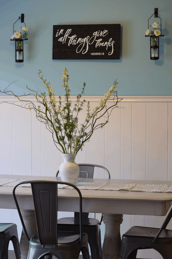 farmhouse dining room table with a white vase and willow stems