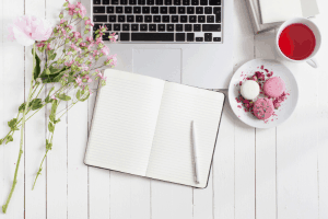getting organized with a flat lay of notebook, laptop, flower bouquet, and cup of tea.