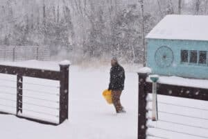 man outside carrying a water bucket in a blizzard to give to the chickens
