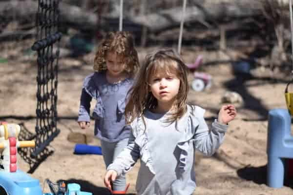 two little girls playing outside in a sand box