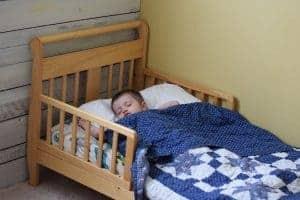 toddler boy sleeping in bed