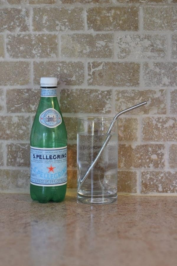 bottle of Pellegrino water with a glass on countertop.