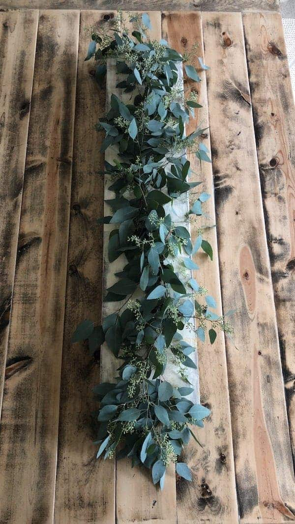 Finished eucalyptus fall tablescape on a wooden board and centered on table