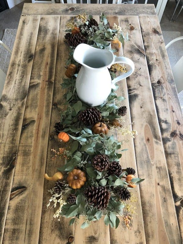 farmhouse table lined with eucalyptus greenery, small pumpkins, and pinecones