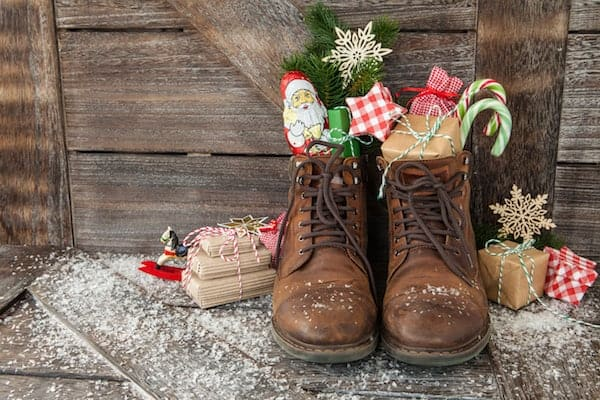pair of brown boots filled with chocolate candies and candy canes to celebrate St. Nicholas Day