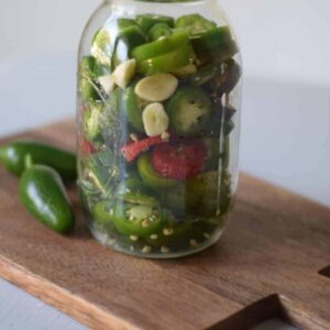 large mason jar full of fermented jalapeños
