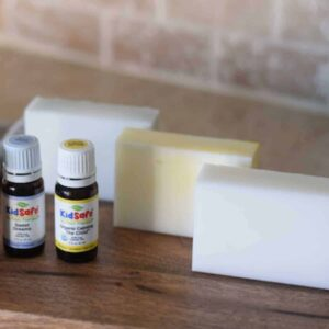 homemade goat milk soap bars on counter with essential oil bottles
